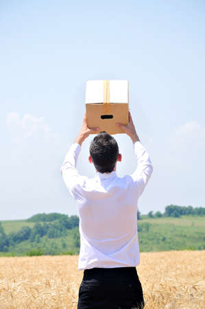 Business man delivering box in wheat Stock Photo - 14464938