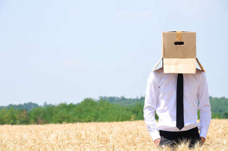 thinking outside the box: Business man hiding face with box