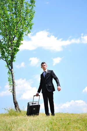 Uomo d'affari con i bagagli in natura