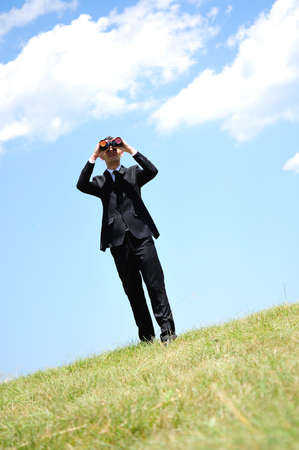 Business man with spyglass in nature photo
