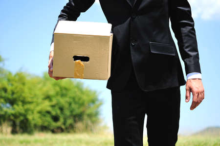 delivery service: Business man delivery box in nature Stock Photo