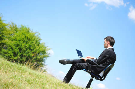 Business man standing on laptop in nature Stock Photo