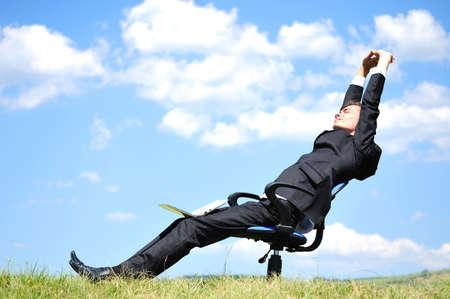 自然の中で椅子の上のビジネスの男性