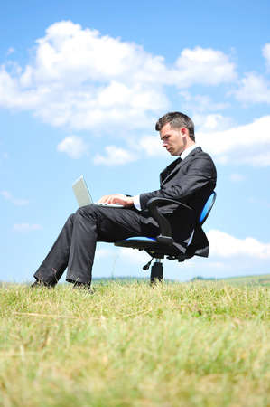 Business man standing on laptop in nature photo