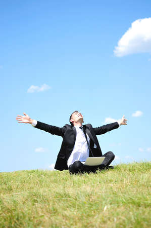 relaxed business man: Business man standing on laptop in nature Stock Photo