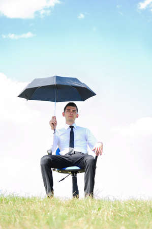 Business man standing with umbrella in nature photo