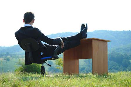 feet on desk: Business man at desk in nature