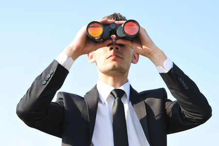 seguridad laboral: Hombre de negocios con binoculares en el cielo
