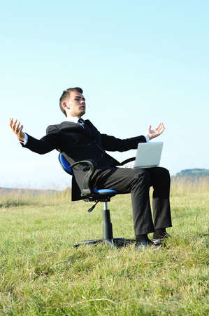Business man with laptop on chair photo