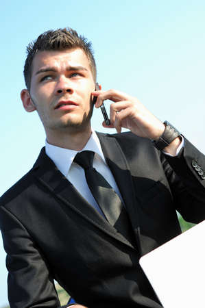 Business man talking at phone on sky photo