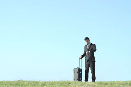 Business man with luggage in nature Stock Photo