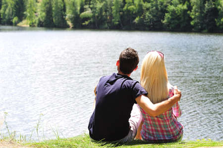 Young couple holding arms at lake photo