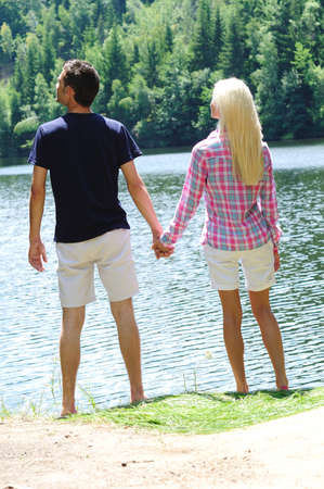 Young couple holding hands at lake photo