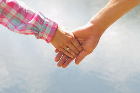 Couple holding hands closeup in nature photo