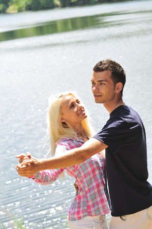 Young couple dancing at lake photo