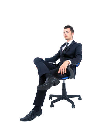 Isolated young business man standing on chair Stock Photo