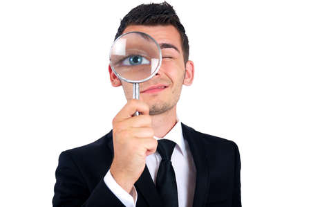 Isolated young business man with magnifying glass