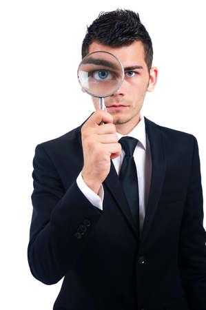 Isolated young business man with magnifying glass photo