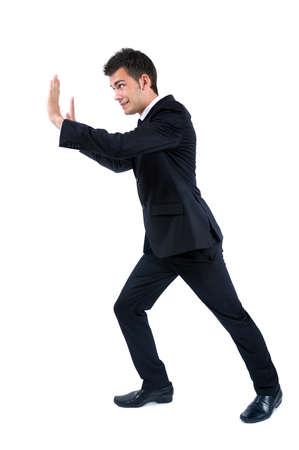 pushing: Geïsoleerde jonge zakenman duwen Stockfoto