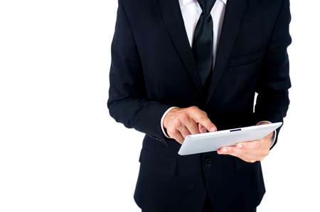 Isolated young business man using tablet Foto de archivo