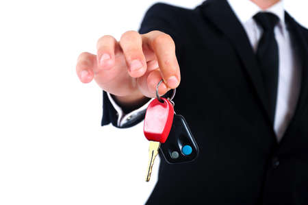Isolated young business man giving car key photo