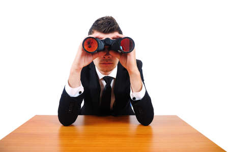 Isolated business man with binocular at desk