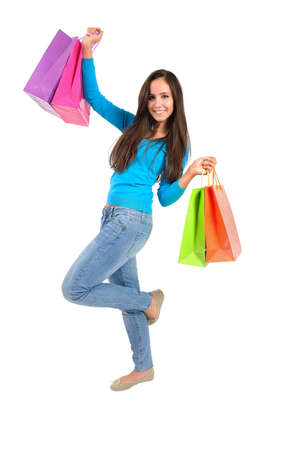 spending full: Isolated casual young woman with shopping bag happy