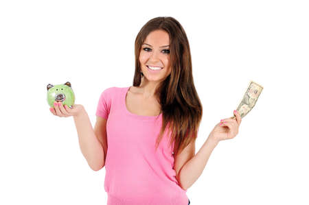 Isolated young casual woman with piggy and money photo