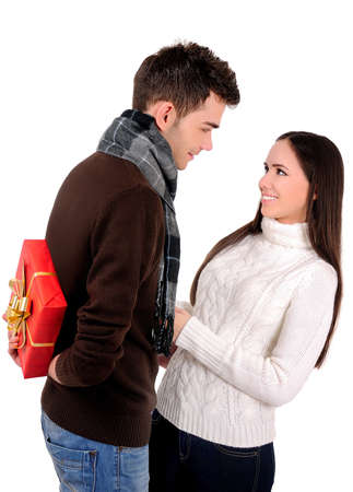 gift behind back: Isolated young casual couple with gift