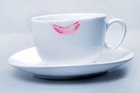 labios sexy: Rosa del l�piz labial en la taza blanca sobre fondo azul