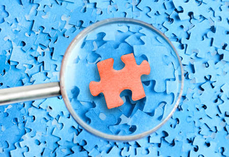 Magnifying glass and piece on a puzzle background  photo