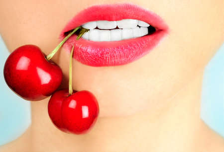 Woman  with cherry on blue background  Stock Photo