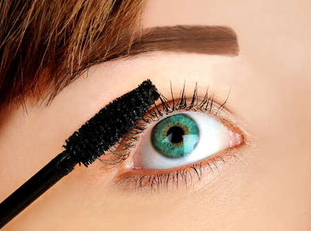 Woman applying mascara on eye photo