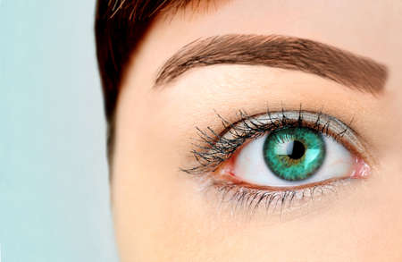 Woman with green eye on blue background  photo