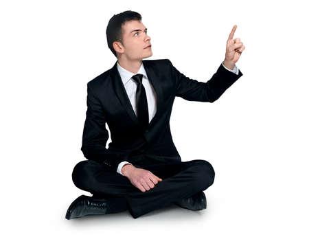 legs folded: Man pointing something on white background Stock Photo