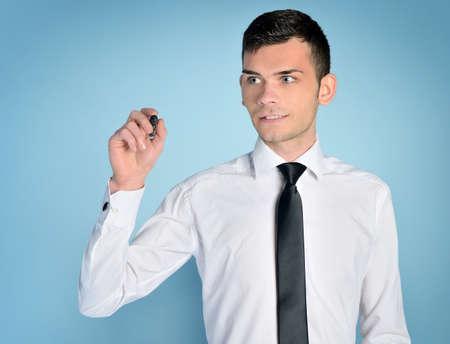 Business man writing on blue background photo