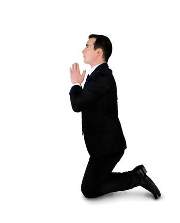 kneel down: Isolated business man pray position