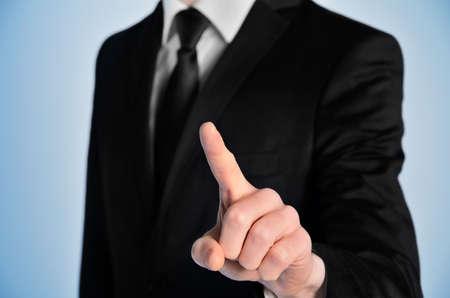 Business man press something on blue background photo