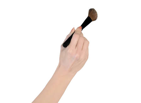 Isolated woman hand holding makeup brush photo