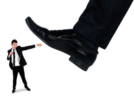 little business man: Isolated feet man crushing little business man Stock Photo