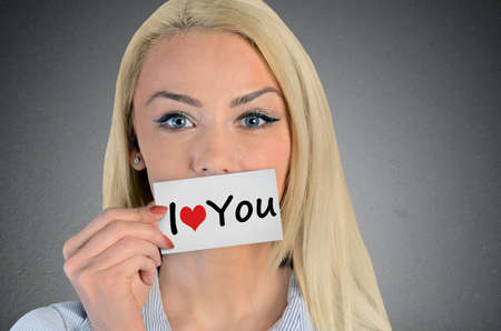 Beautiful woman holding card with I love you word