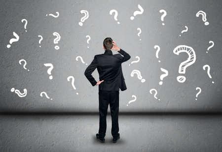 signo de interrogación: Joven hombre de negocios de escritura signo de interrogación en la pizarra