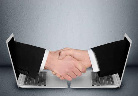 stretta di mano: Gli uomini d'affari della stretta di mano tramite computer Archivio Fotografico