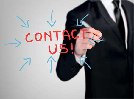 write us: Business man close-up write Contact Us word