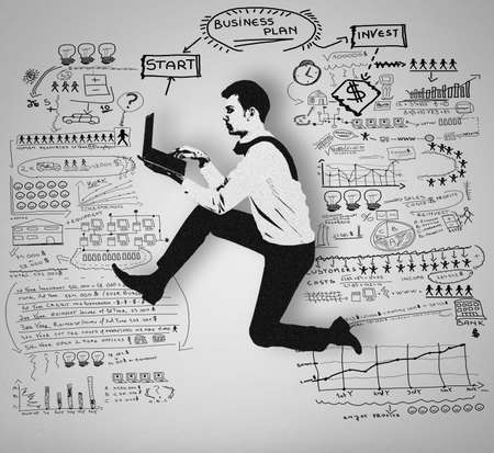man using computer: Man using computer and business plan on wall
