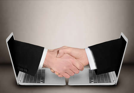 Business people handshake through computer Stok Fotoğraf