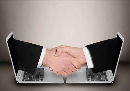 Business people handshake through computer Foto de archivo