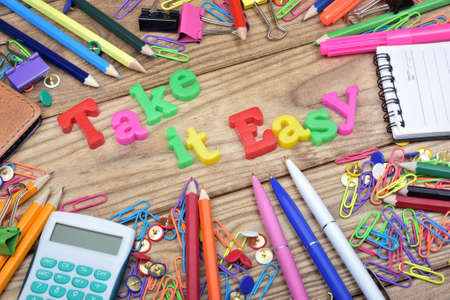 take it easy: Take it Easy word and office tools on wooden table