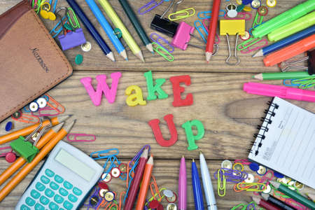 Wake up word and office tools on wooden table Stock Photo