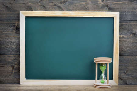 antique sleigh: School board and hourglass on wooden table Stock Photo
